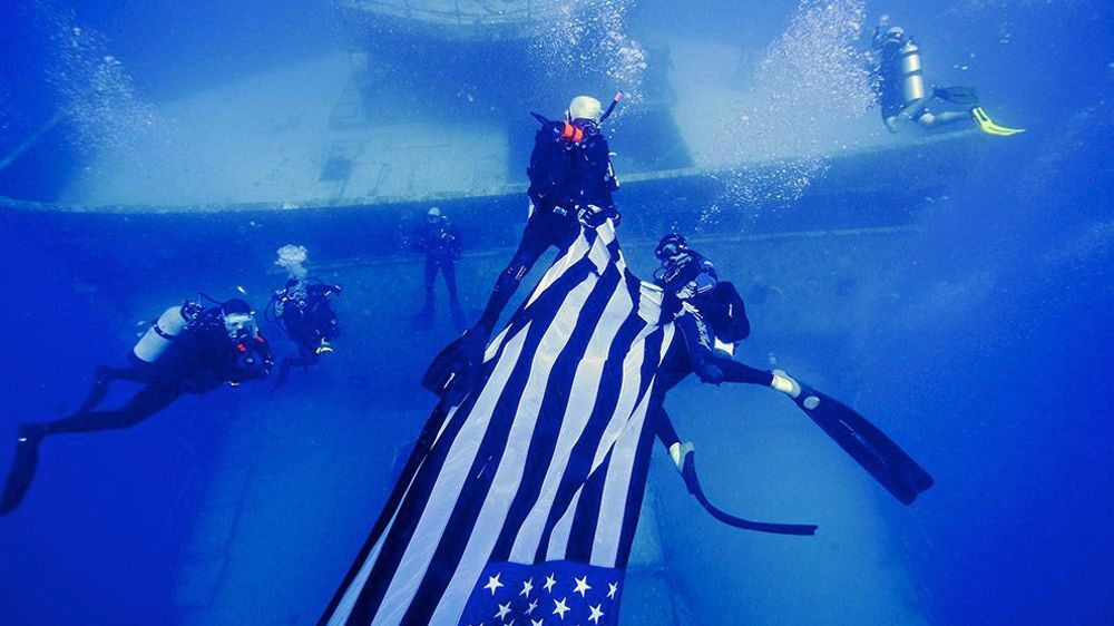 Divers carrying flag near shipwreck